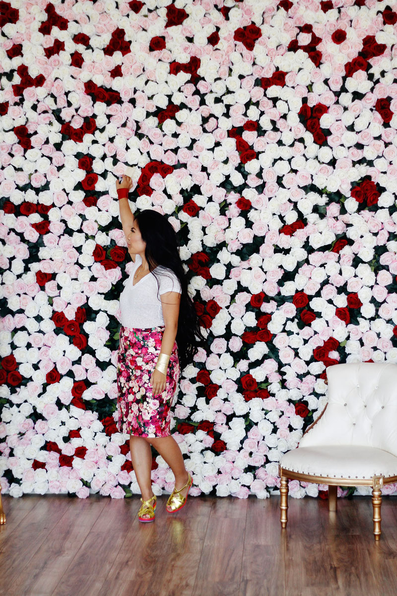 Portrait of Krista Suh in front of a wall of roses