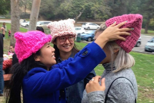 Krista Suh adorns MILCK with a pussyhat while Yumi Sakugawa observes
