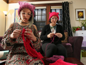 Mary Bethel (right) and her daughter, Kazia, 10, stitch pink hats