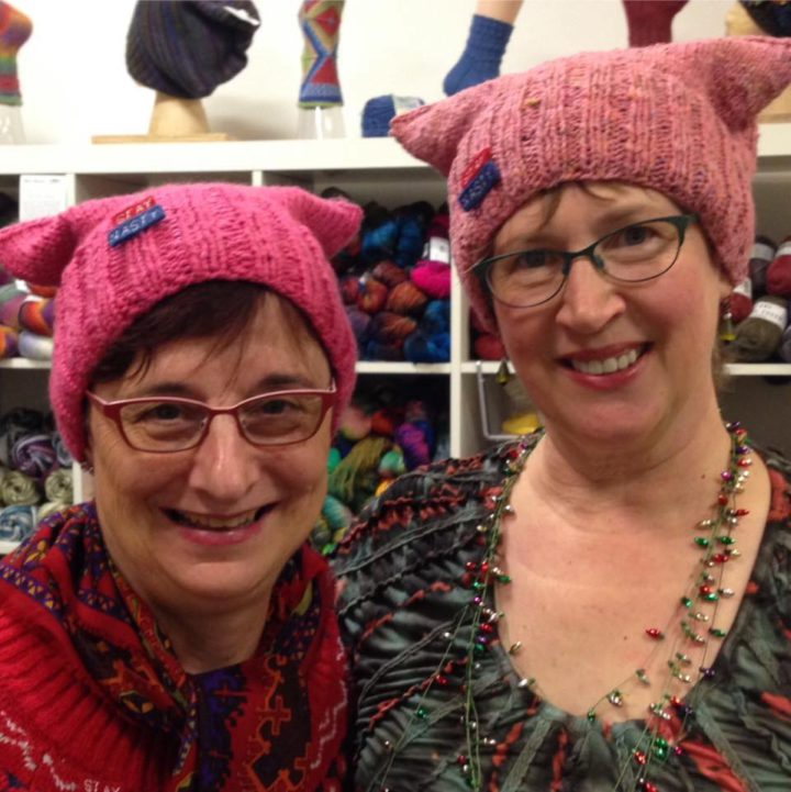 Celia McCarthy and Pamela McKinstry, co-owners of Piedmont Yarn in Oakland, show off the pussy hats they made